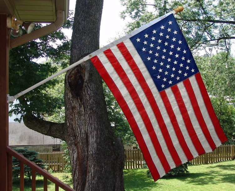 Mounted flagpole to side of house